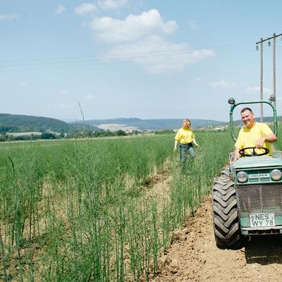 Mann mit Traktor und Frau auf einem Feld