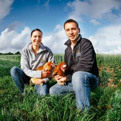 Frau und Mann knieen in einer Wiese und haben je ein Huhn in den Armen