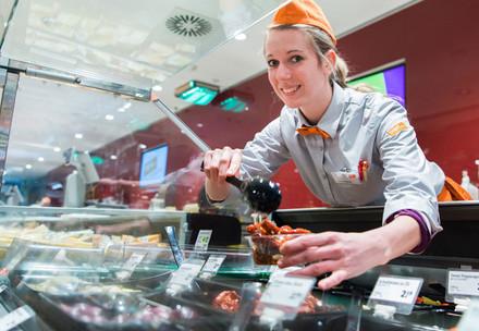 Mitarbeiterin steht hinter Frischetheke und hält eine Schale mit Fleisch in den Händen