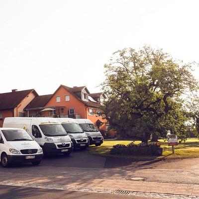 vier weiße Kleinbusse vor einem Haus