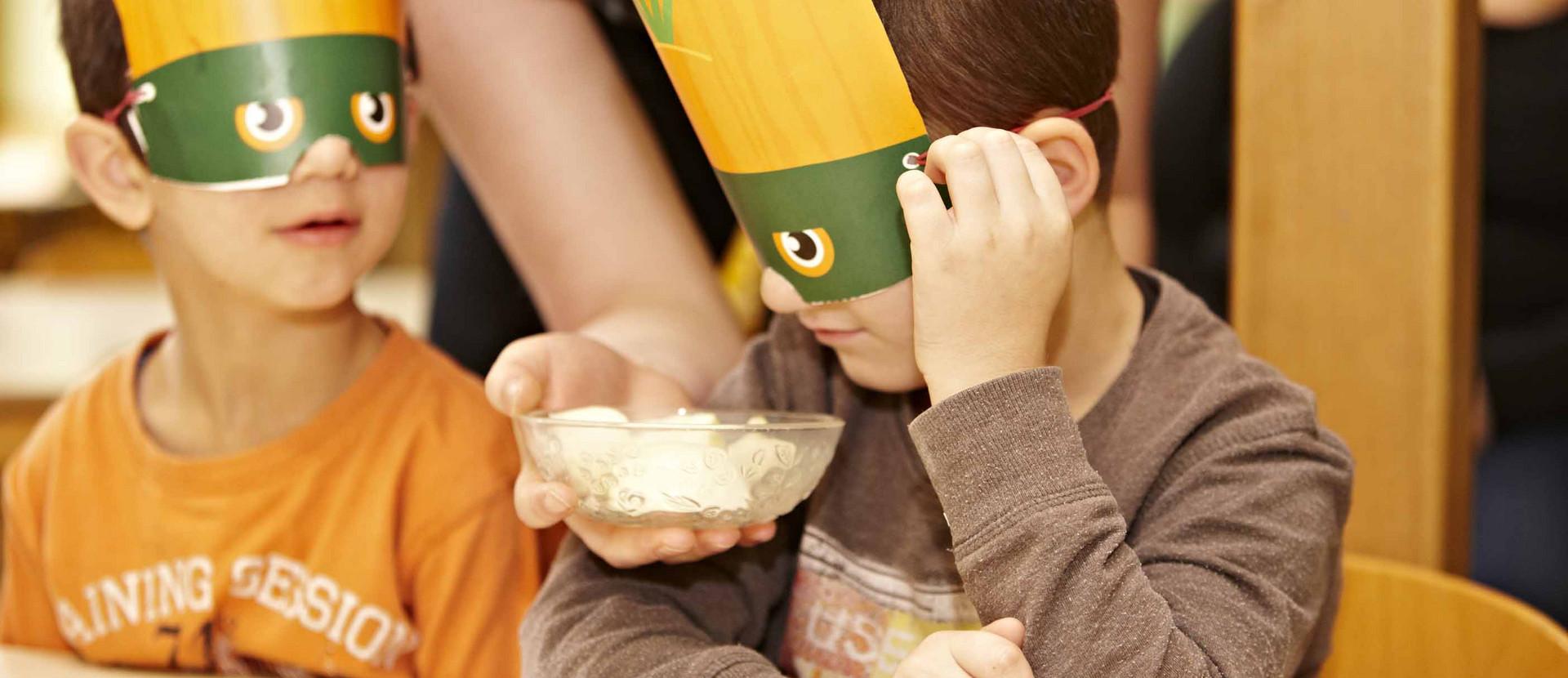 Junge mit Maske vor den Augen riecht an Lebensmitteln in einer Schüssel