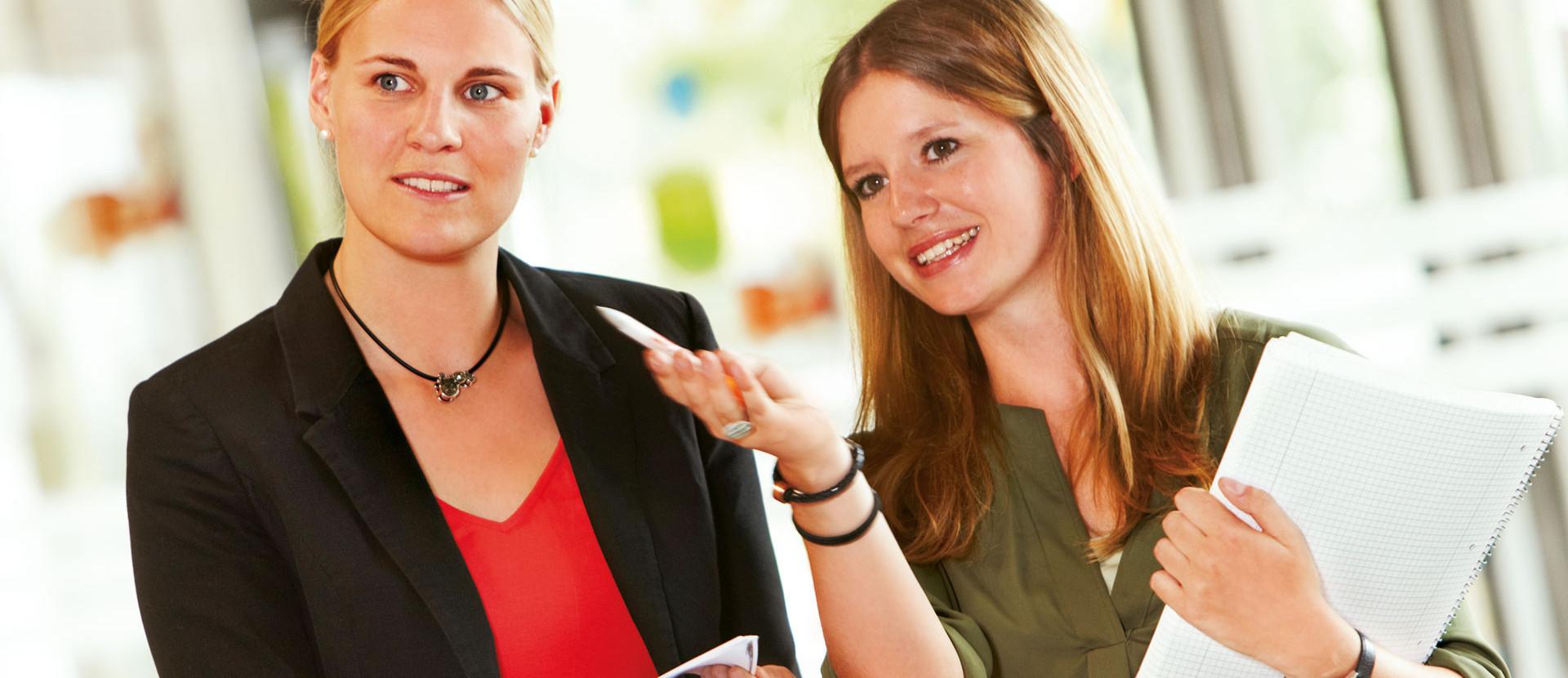 zwei Mitarbeiterinnen mit Stift und Unterlagen in den Händen