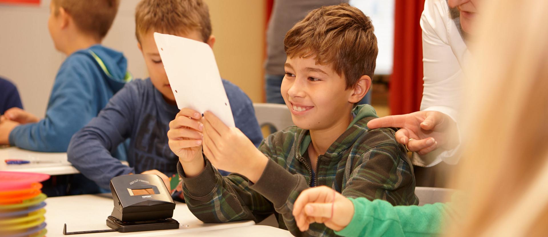 lächelnder Junge hält Maske in der Hand und schaut sie an