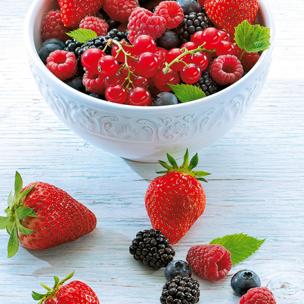 Eine Schale voller Erdbeeren, brombeeren, Himbeeren, Preiselbeeren und Blaubeeren. Daneben liegen auch noch ein paar Exemplare dieser Beeren.