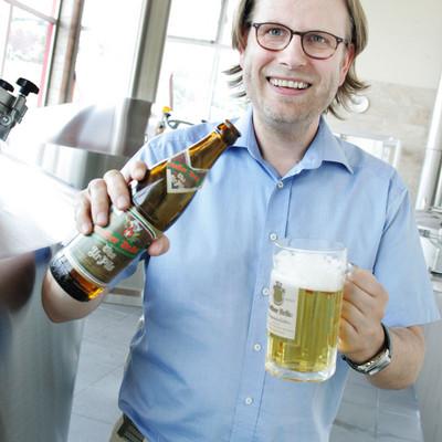 Mann schenkt Bier in Glas ein