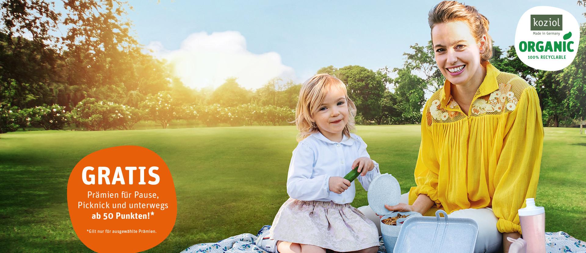 Frau sitzt mit Mädchen auf einer Picknickdecke auf einer Wiese
