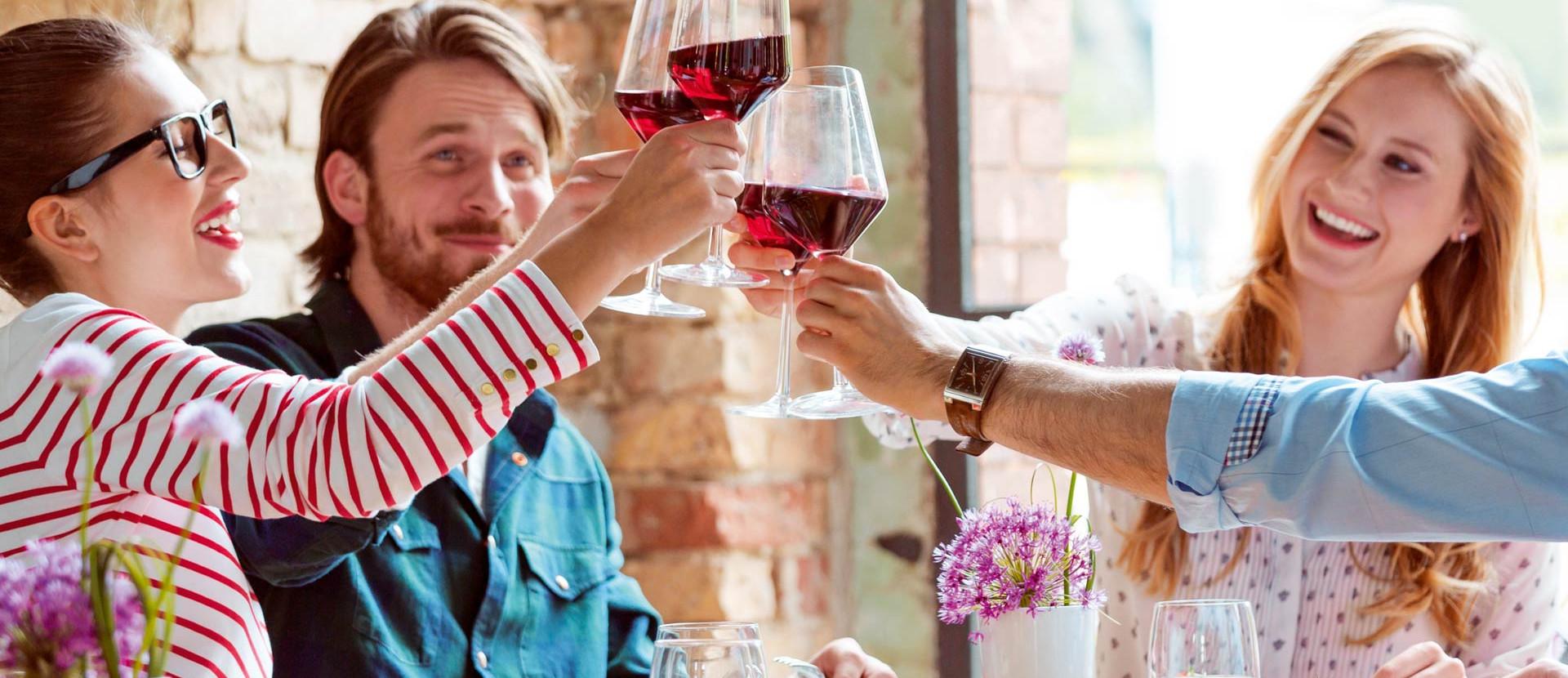 Zwei Paare am Tisch stoßen mit Weingläsern an