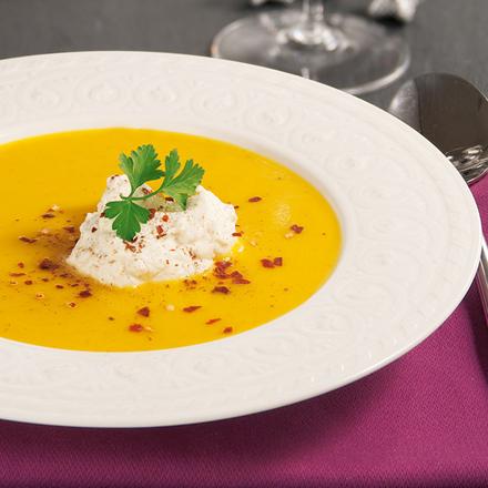 Kürbissuppe auf weißem Teller auf einer purpurfarbenen Tischdecke.
