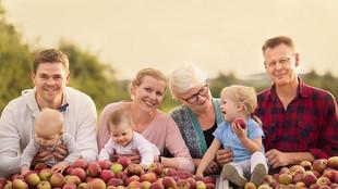 Die Familie Münch, vier Erwachsene und drei Kleinkinder, posieren hinter mit Äpfeln aufgeschütteten Kisten