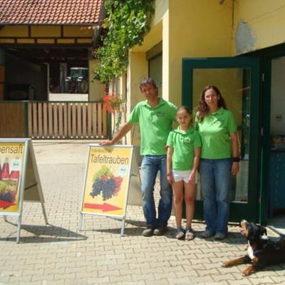 Mann, Frau, Mädchen und Hund im Hof vor dem Traubensaft- und Tafeltrauben-Laden