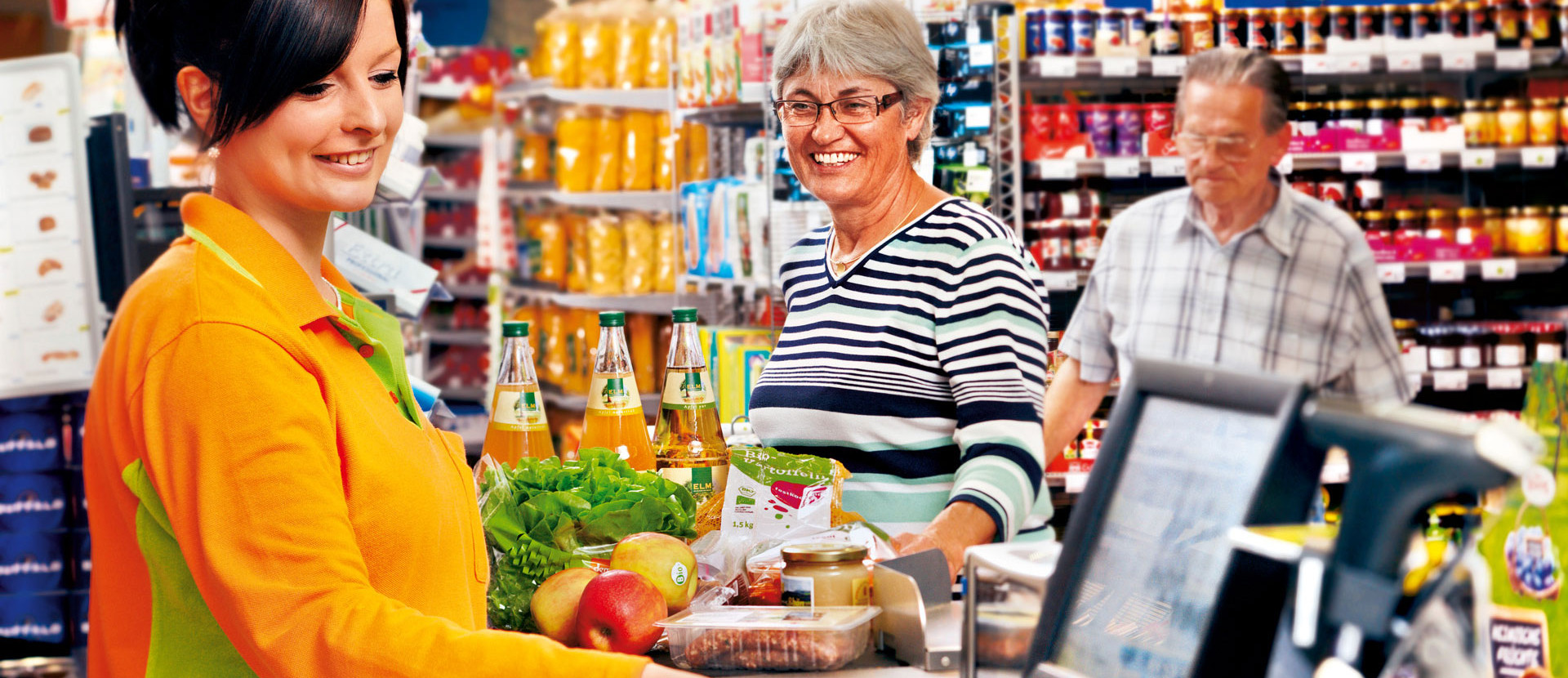 Mitarbeiterin an Kasse mit Kunden