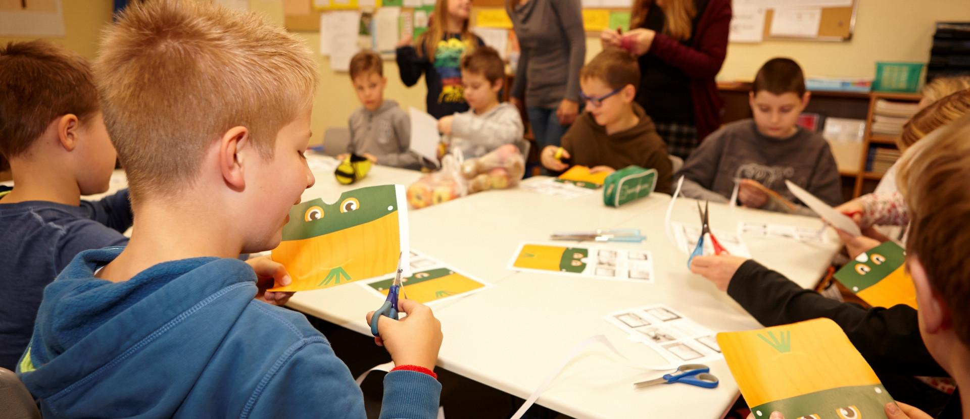 Kinder sitzen am Tisch und schneiden Masken aus