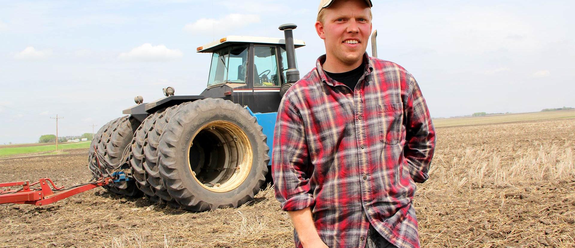Bauer vor Traktor auf Feld