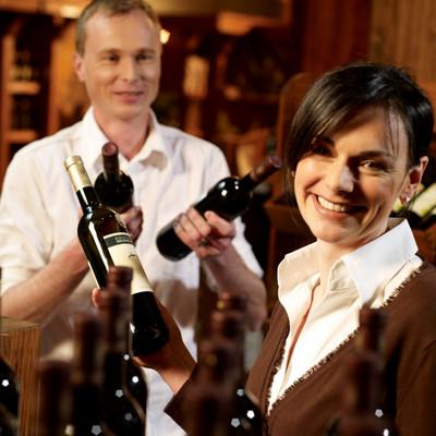 Mann und Frau mit Weinflaschen in den Händen