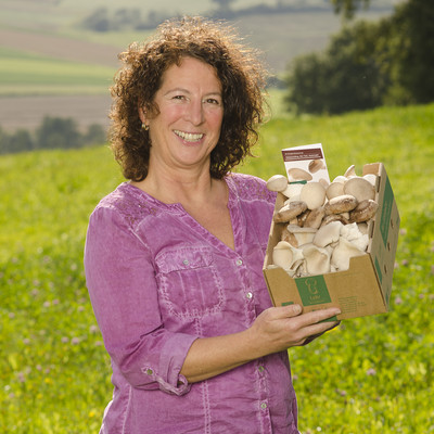 Frau steht auf einer Wiese mit einem Karton Pilzen in den Händen
