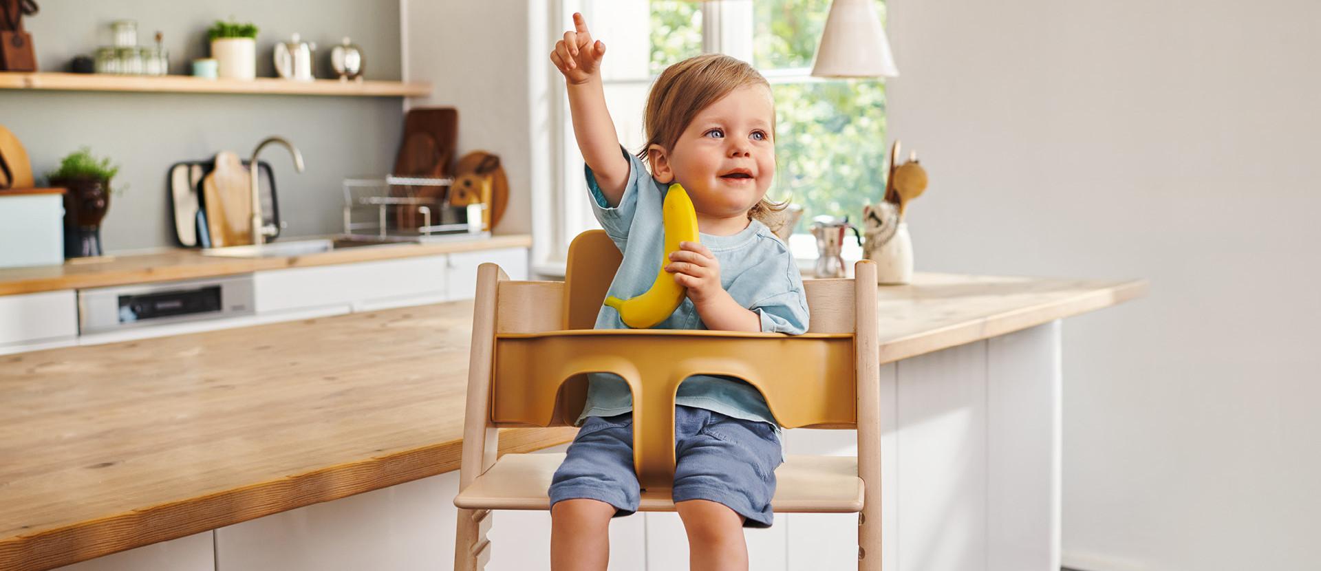 kleines Mädchen sitzt Banane in einem Hochstuhl