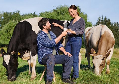 Fairness Frau und Mann mit Kuh und Milchglas auf Weide