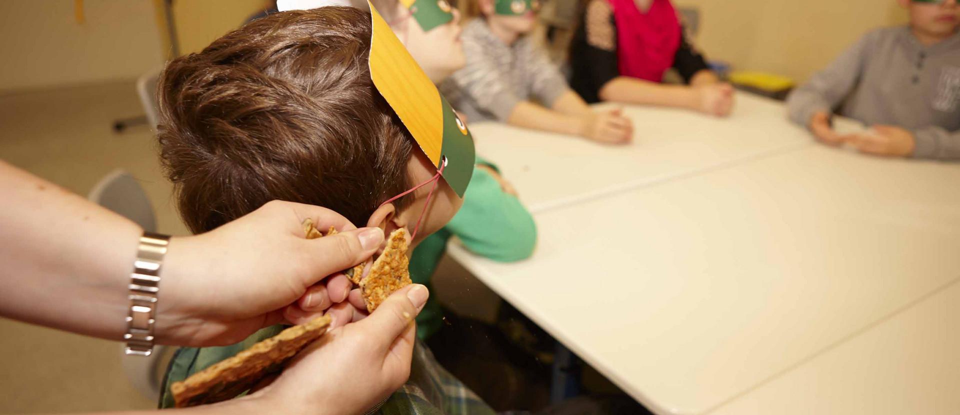 Junge mit Maske hört das Knacken eines Knäckebrot