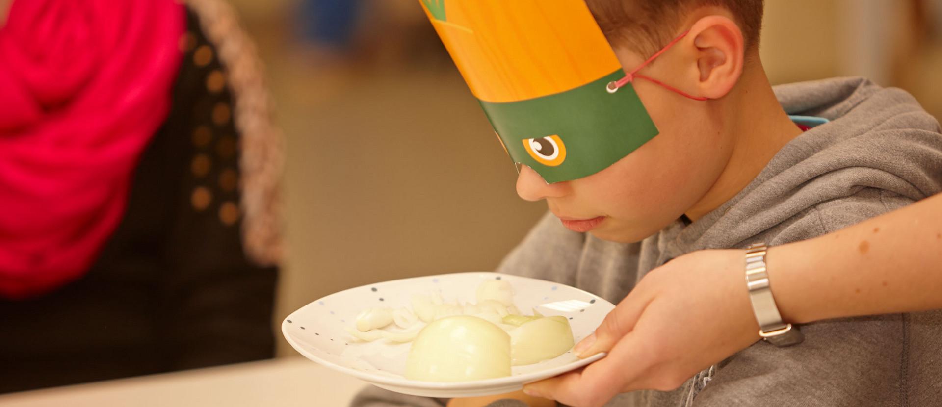 Junge mit Maske riecht an Zwiebeln, die auf einem Teller liegen