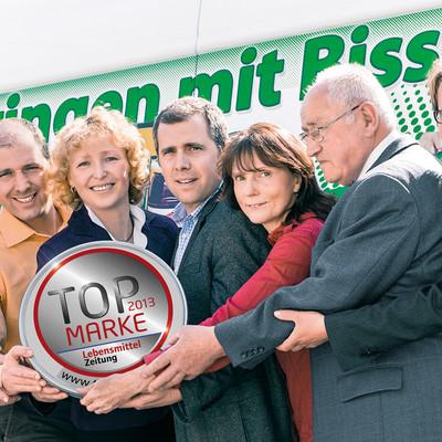 Mitarbeiter der Schweizer Sauerkonserven halten Auszeichnung Topmarke in den Händen