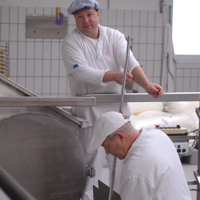 zwei Pordduktionshelfer bei der hessischen Handkäse Herstellung