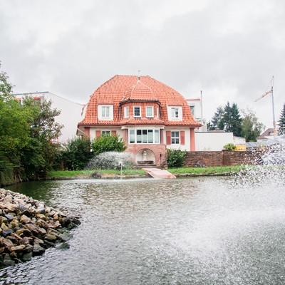 Außenaufnahme Villa mit Teich davor