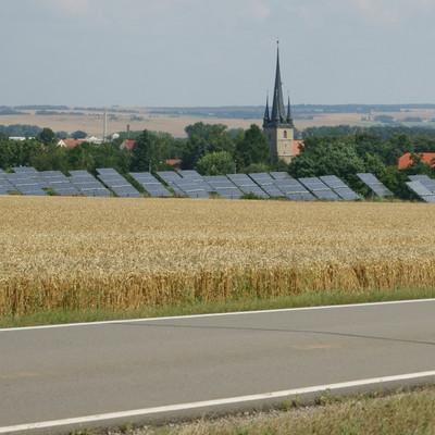 eine Straße, ein Feld, Solaranlagen und eine Kirche im Hintergrund