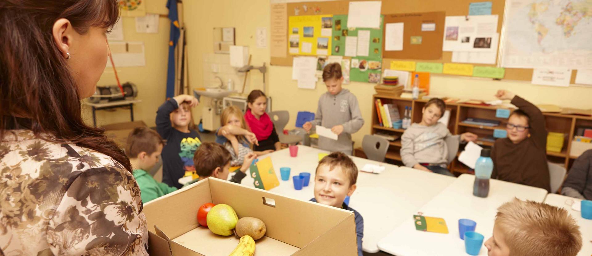 Frau steht mit Karton mit Obst in einem Klassenraum mit Schülern