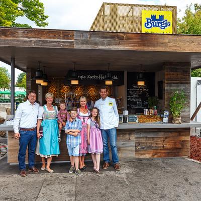 Familie vor Verkaufsstand Kartoffelkuchl