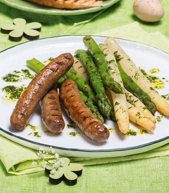 Lamm-Bratwürstchen mit grünem und weißem Spargel auf einem Teller
