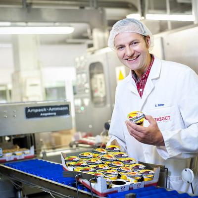 Mitarbeiter steht an einem Förderband einer Abfüllmaschine für Joghurt