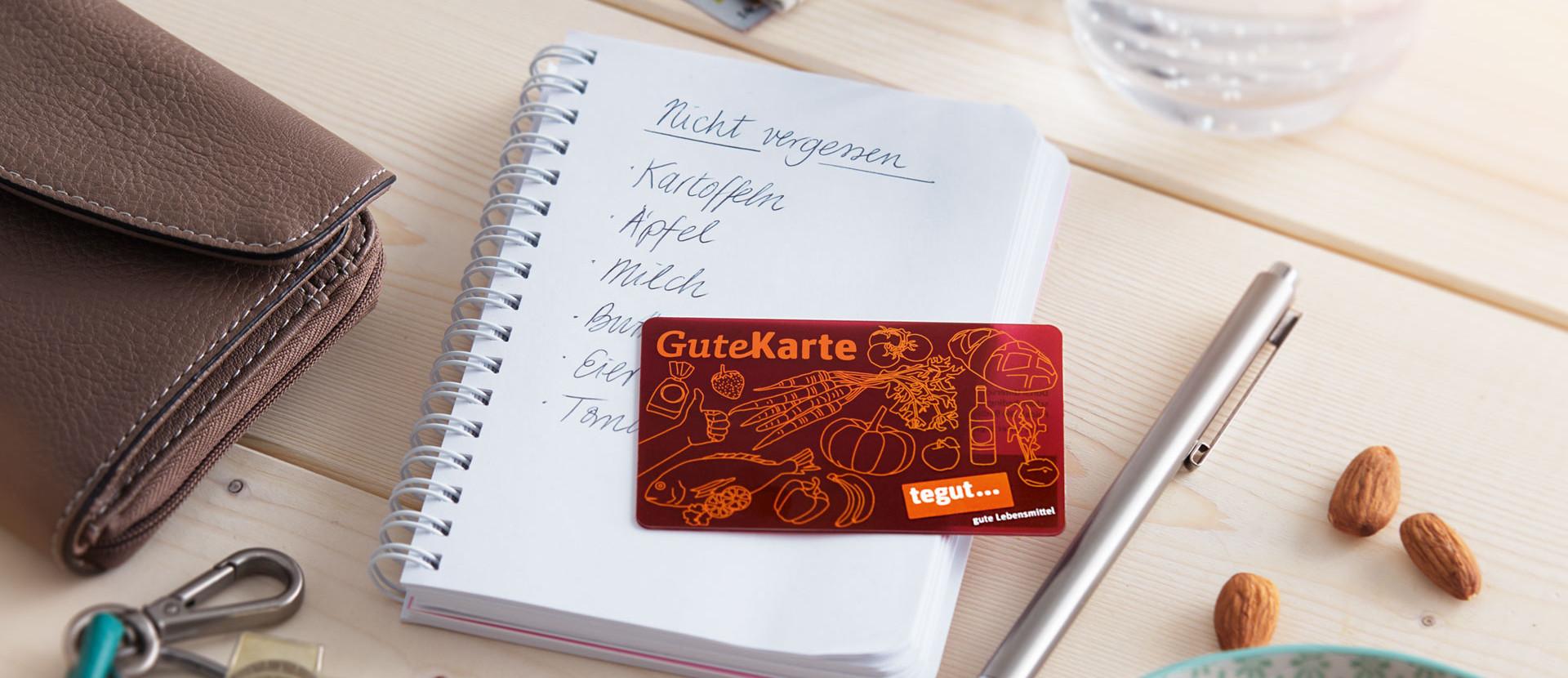 tegut... Kundenkarte GuteKarte zum Sparen beim Einkaufen liegt auf Schreibtisch. Daneben ein Stift, Geldbörse, Einkaufsblock und ein paar leckere Nüsse.