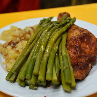 Teller mit grünem Spargel, Fleisch und Bratkartoffel