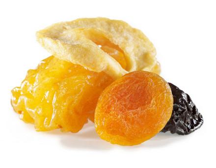 ein Mix aus Früchten bestehend aus einem getrockneter Apfelring, einem getrockneter Pfirsisch, einer getrocknete Pflaume und einer getrocknete Aprikose