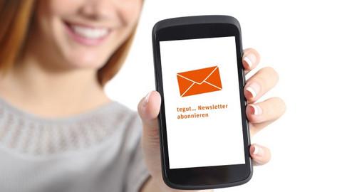"Frau hält Handy mit Text ""tegut... Newsletter abonnieren"" ins Bild"