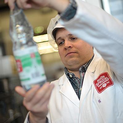 Mann kontrolliert eine abgefüllte Wasserflasche