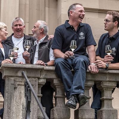Mitarbeiter des Juliusspital auf einem Balkon mit Weingläsern in den Händen