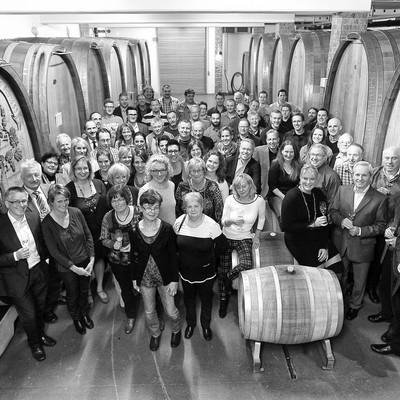 Gruppenfoto im Weinkeller zwischen großen Weinfässern