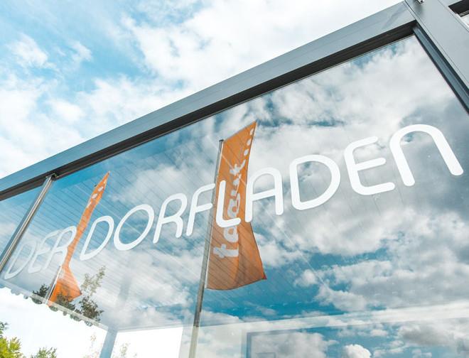 """""""Der Dorfladen"""" Schriftzug an Eingangsscheibe"""