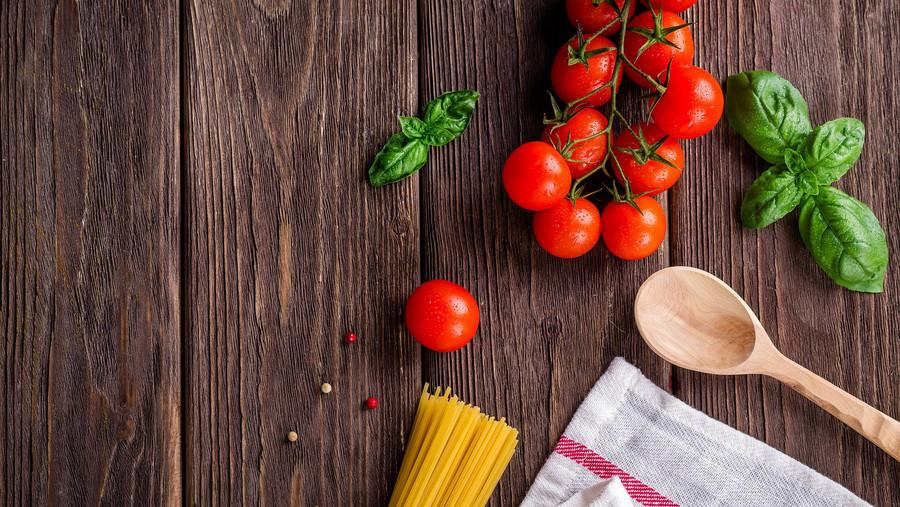 Tomaten, Nudeln, Basilikum, Holzlöffel und Geschirrtuch liegen auf einem Holzboden