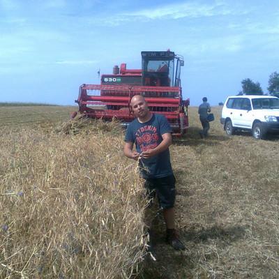 Bauer Maier steht auf einem Feld vor einem Mähdrescher
