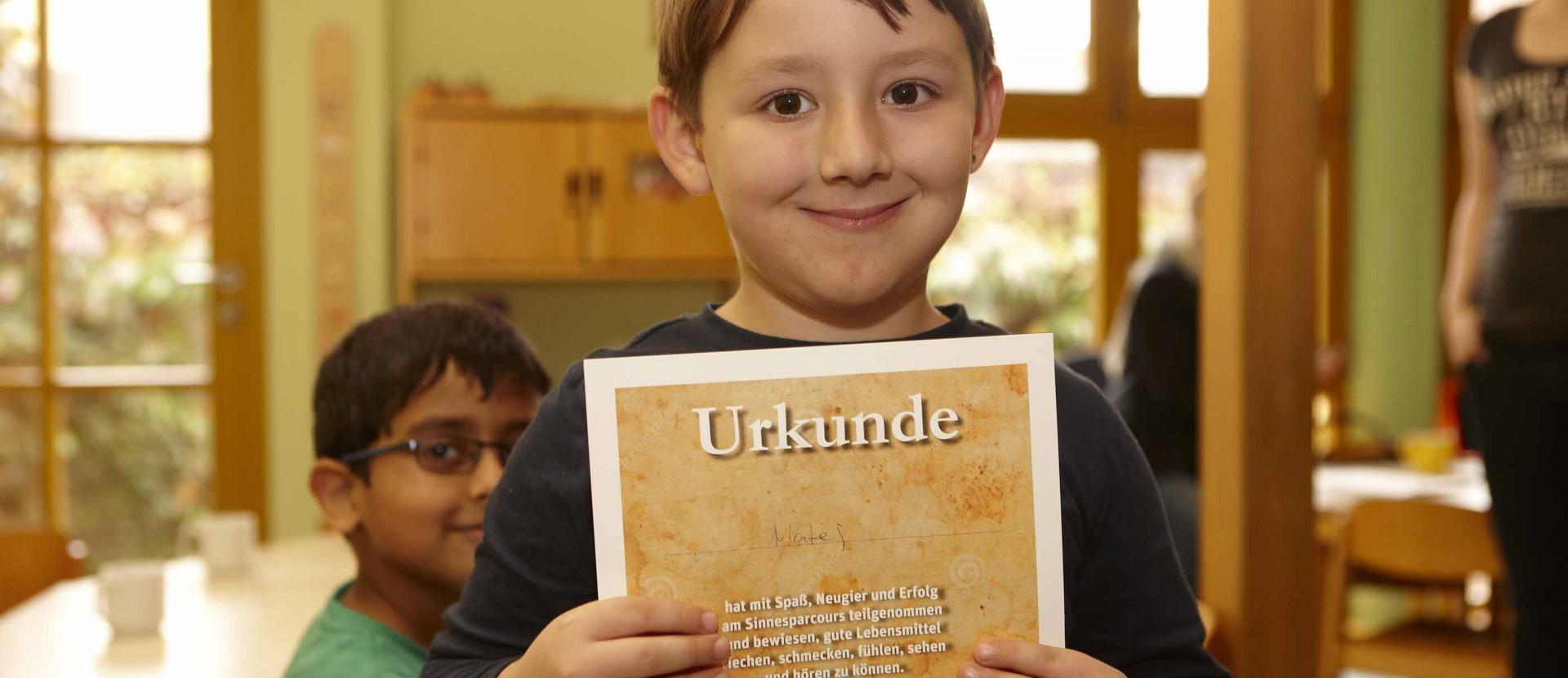 Junge hält Urkunde in der Hand