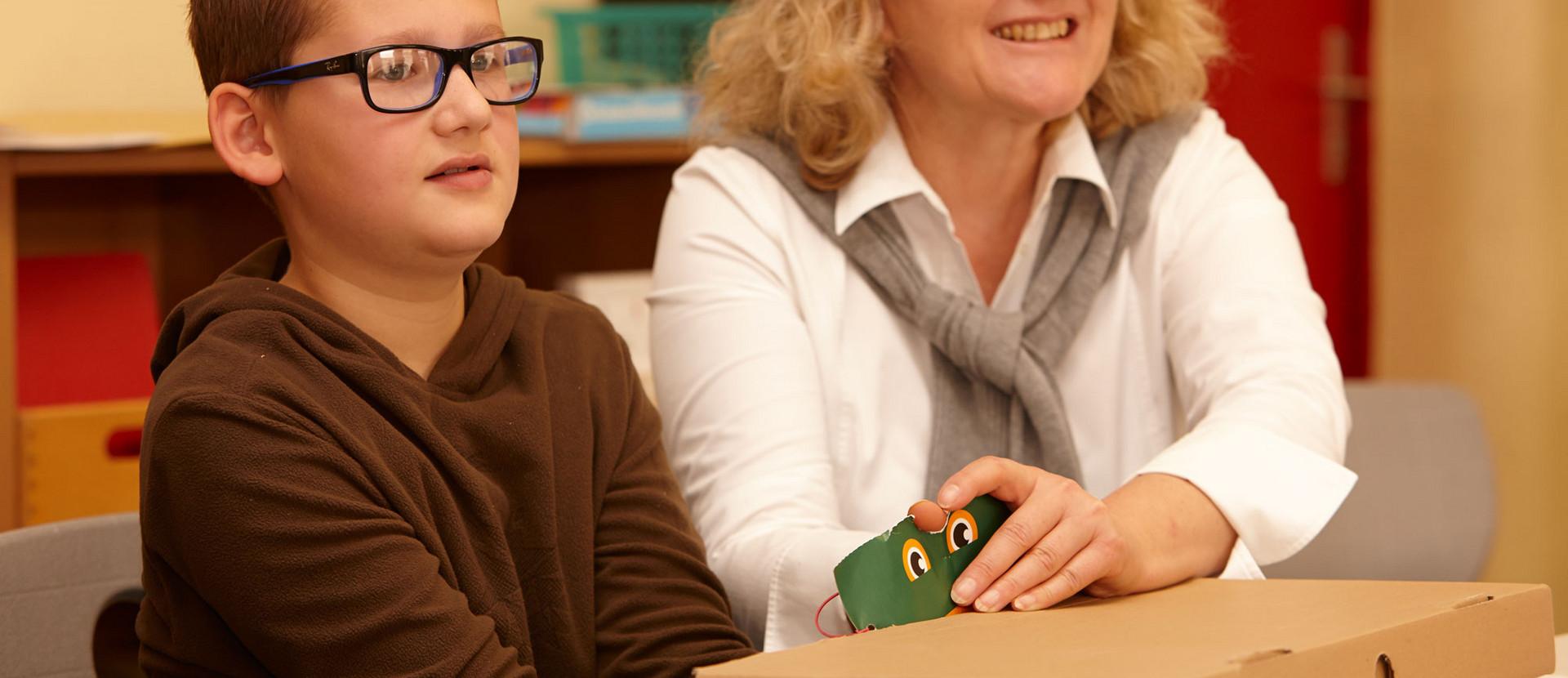 Junge neben einer Frau ertastet in einem Karton Lebensmittel