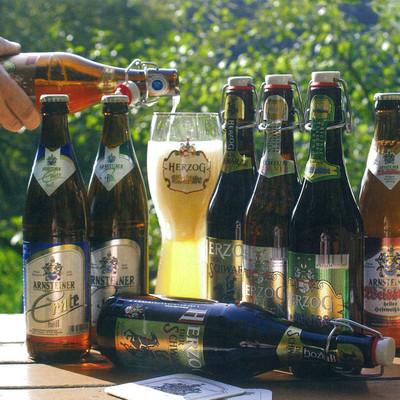 Einige Flaschen Herzog Bier auf einem Tisch im Garten