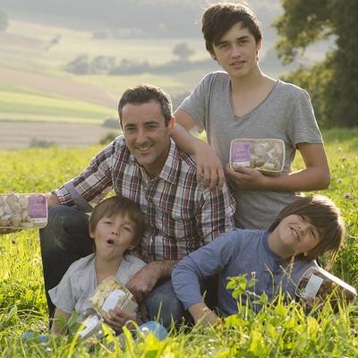 Mann sitzt mit Söhnen auf einer Wiese und sie halten Packungen mit Pilzen in den Händen