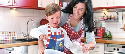 Frau füllt mit Sohn in Küche Mehl in eine Schüssel