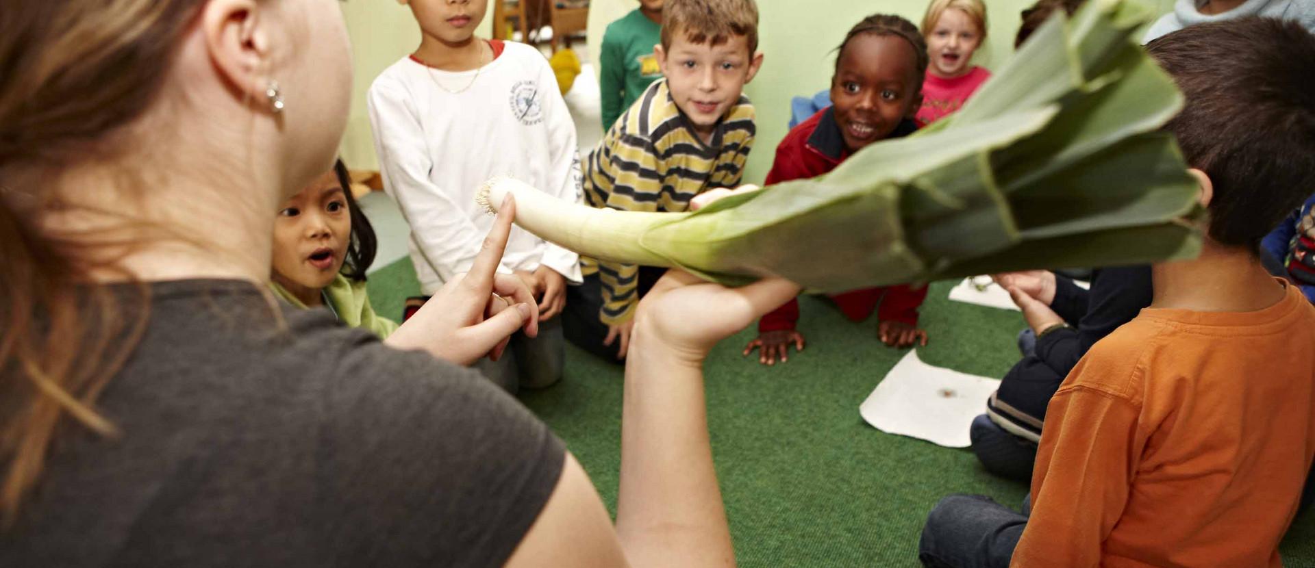 Frau zeigt Kindern eine Stange Lauch