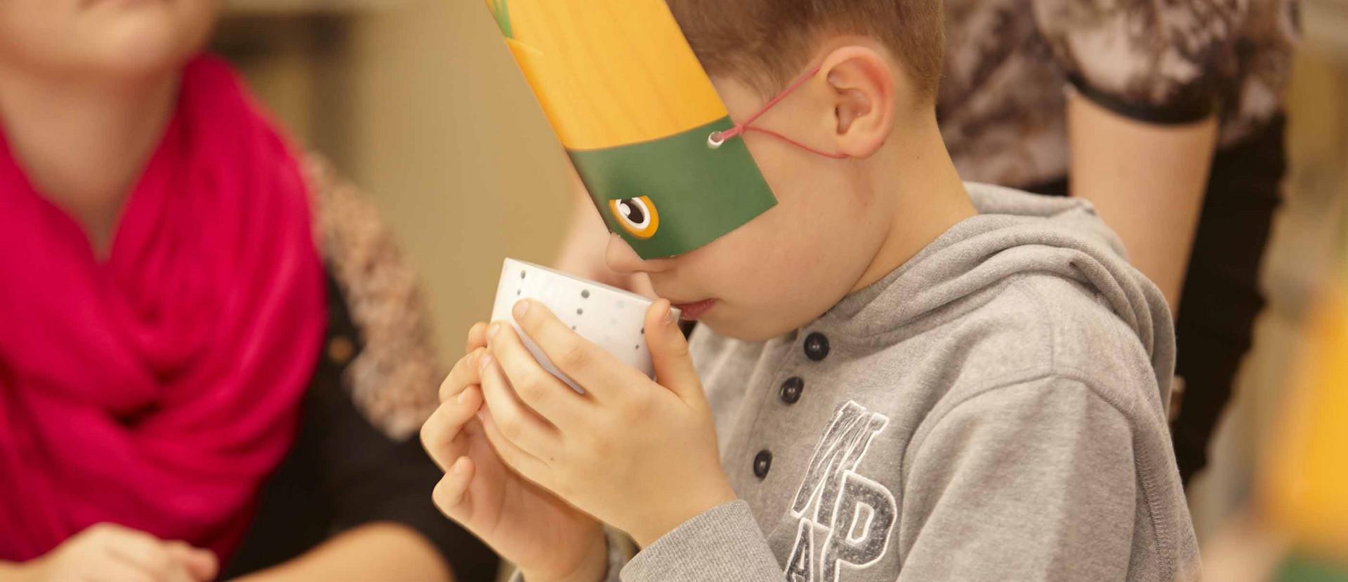 Junge mit Maske riecht an Lebensmitteln in einer Tasse
