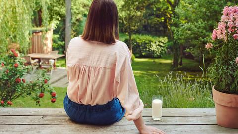 Regionale Produkte Frau sitzt auf Holzterrasse mit Glas Milch
