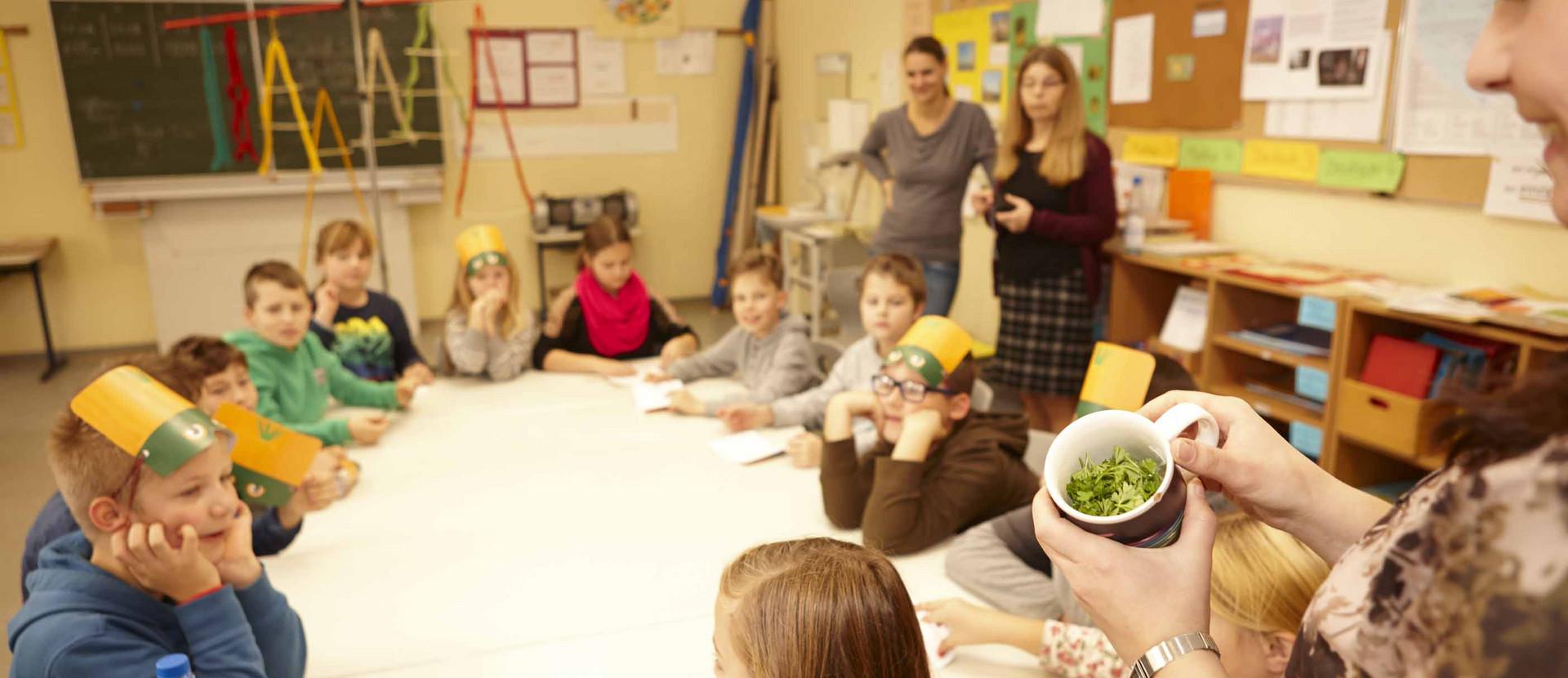 Kinder sitzen an Tischen in der Schule